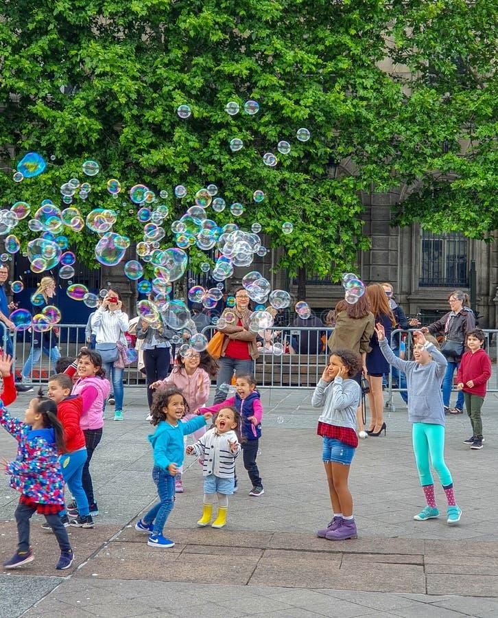 Paris, France, June 2019: Children enjoying bubbles show on the Place de l`Hotel de Ville stock photography
