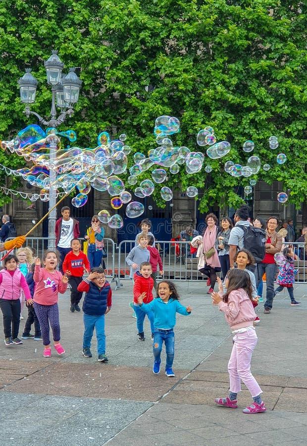 Paris, France, June 2019: Children enjoying bubbles show on the Place de l`Hotel de Ville royalty free stock images