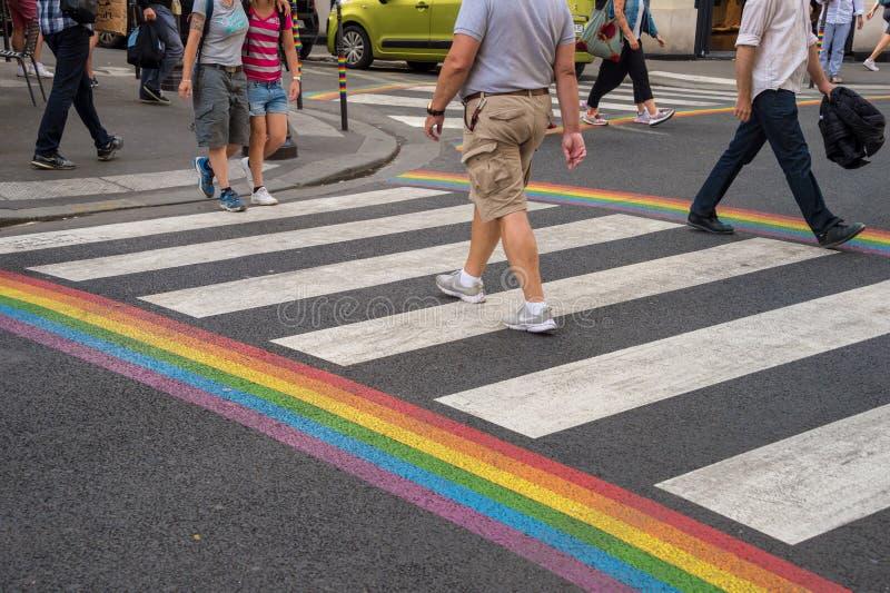 Gay pride flag crosswalk in Paris gay village with people crossing. Paris, France - 24 June 2018: Gay pride flag crosswalk in Paris gay village with people royalty free stock photography
