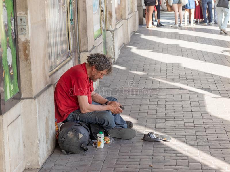Homeless man sitting on the sidewalk in Paris stock photography