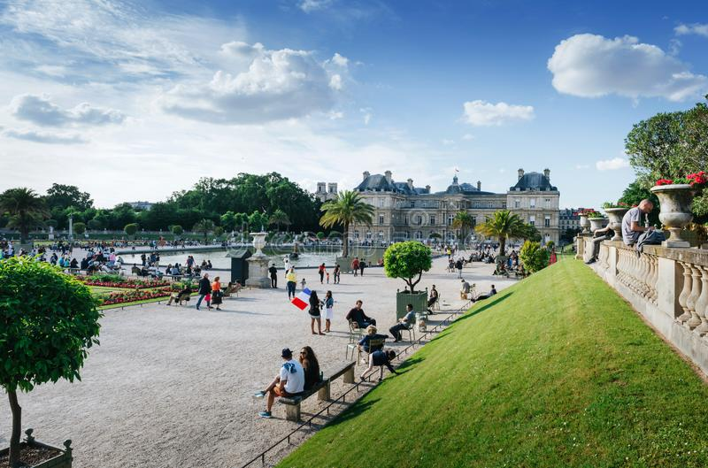 PARIS, FRANCE - JUNE 26, 2016: People relax and hang out in pucturesque park in front of Palais du Luxembourg or Luxemburg Palace royalty free stock images