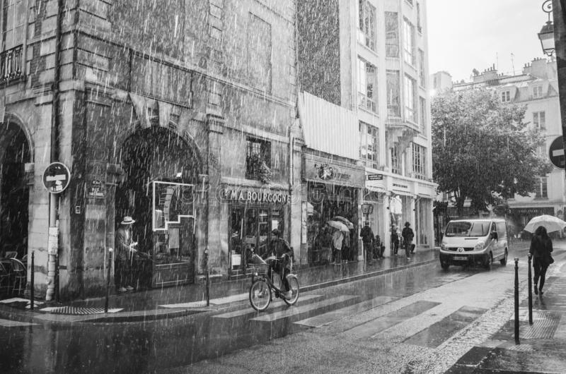 PARIS, FRANCE - JUNE 27, 2016: People on the street Rue des Francs Bourgeois during summer rain. Candid scene stock image