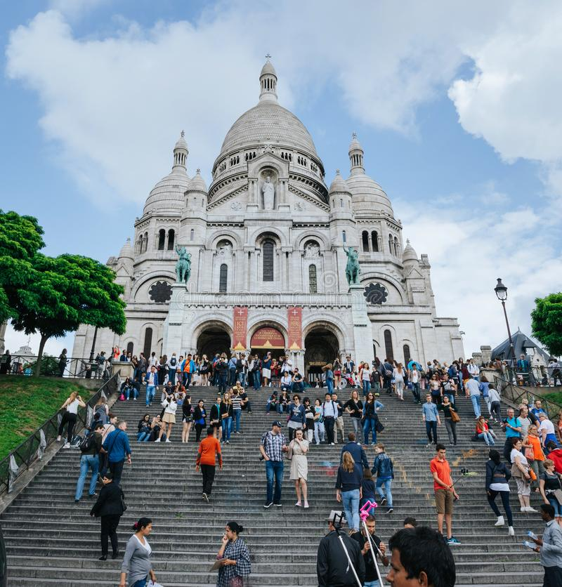 PARIS, FRANCE - JUNE 26, 2016: People walk near Sacre Coeur de Montmartre cathedral. It is a famous catholic church and popular royalty free stock photo