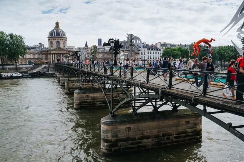 PARIS, FRANCE - JUNE 25, 2016: People walking at the Pont des Arts, bridge with contemporary statues and installations stock photo