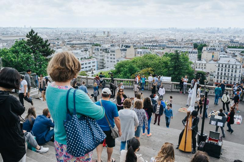 PARIS, FRANCE - JUNE 26, 2016: Tourists near Sacre Ceour de Montmartre cathedral. View of the city from hill viewpoint. Man, royalty free stock photography