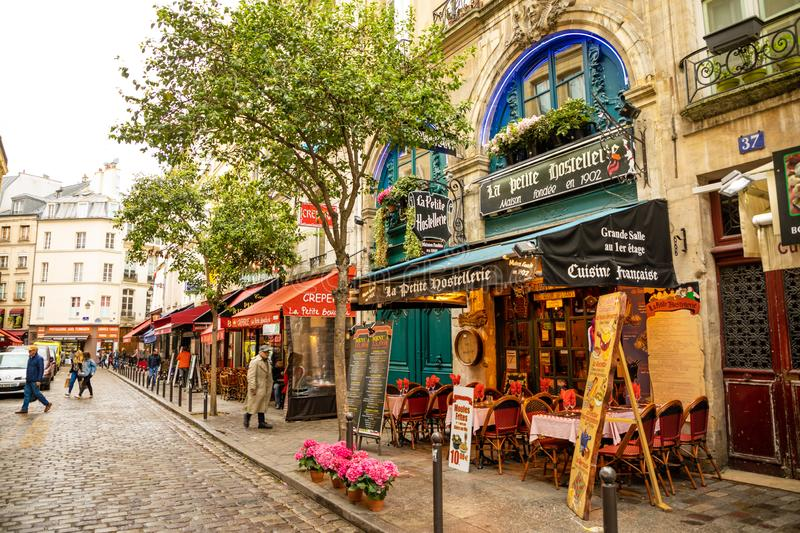 Paris, France - 24.04.2019: Latin Quarter. Narrow street of Paris among old traditional parisian houses and cafe in royalty free stock images