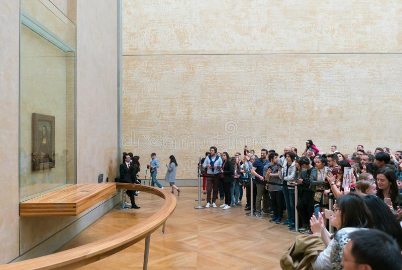 Paris, France - March 31, 2019: a crowd of tourists watch and photograph on smartphones a picture of Leonardo da Vinci stock photography