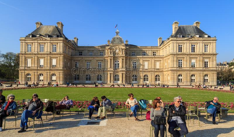 Paris, France, March 27 2017: People enjoy sunny day in the Luxembourg Garden in Paris. Luxembourg Palace is the royalty free stock image