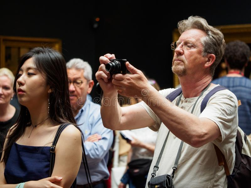 Man photographs painting next to Asian woman, Musee d`Orsay, Paris, France stock photos