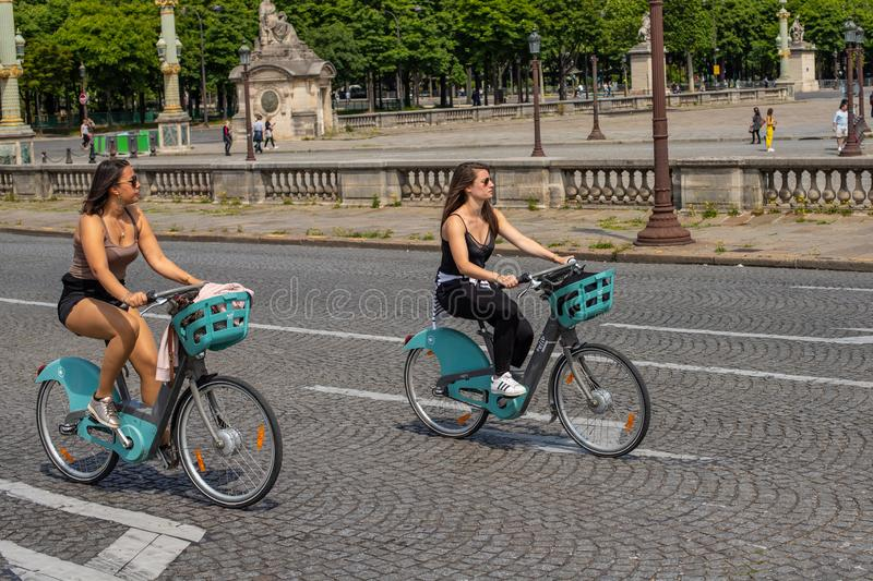 PARIS, FRANCE - MAY 25, 2019: Girls cycling down the street. The public bike system in Paris royalty free stock photos