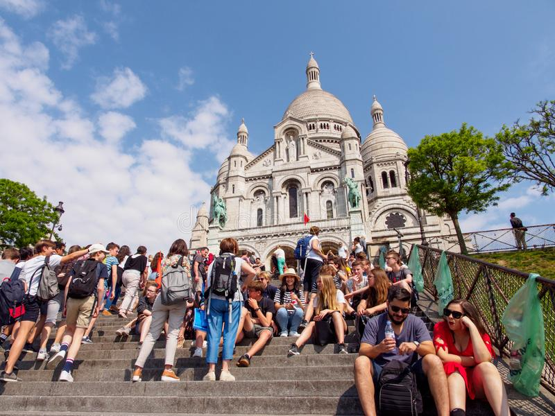 Students sit in front of Sacre Coeur, Montmarte, Paris, France stock image