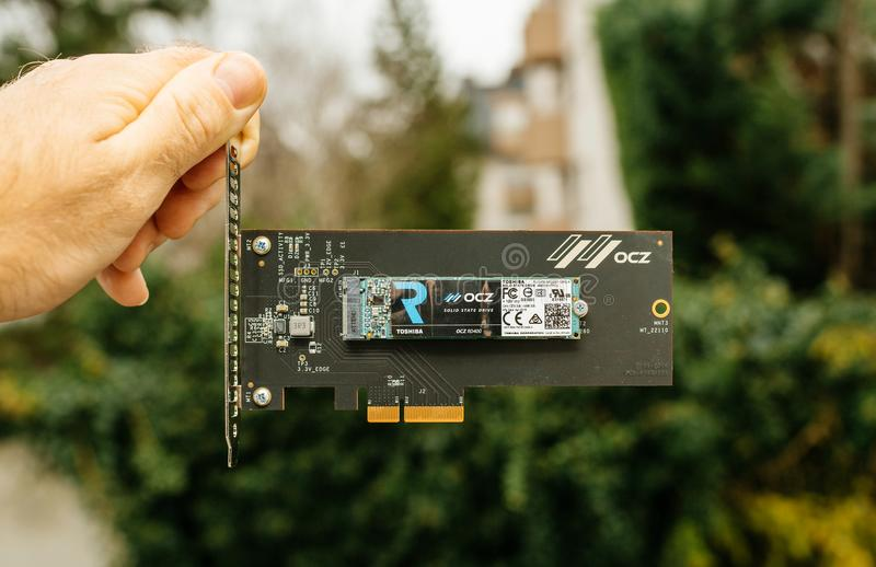 Man hand holding NVME PCIE SSD hard drive disk with itsh adapter. PARIS, FRANCE - NOV 28, 2017: Man hand holding NVME PCIE SSD hard drive disk with itsh adapter royalty free stock photography