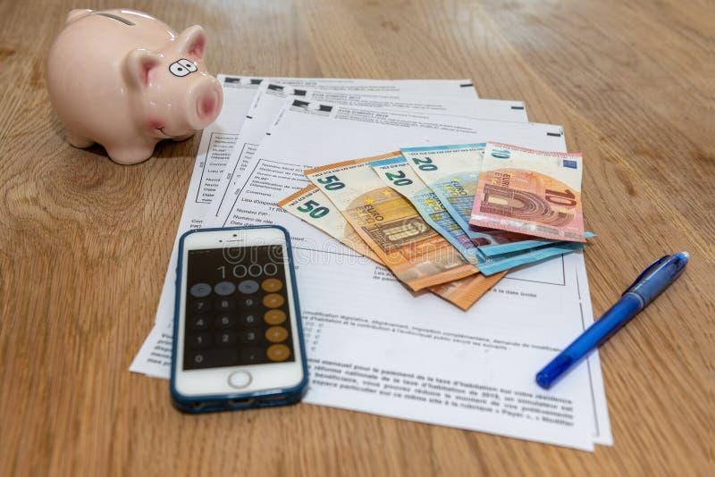 Paris, France - 15 novembre 2018 : La diverse déclaration d'impôt française, la tirelire et les billets de banque dans les euros images stock
