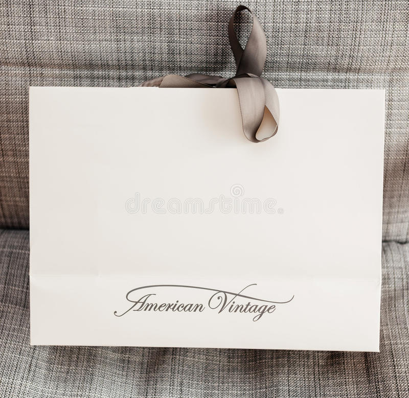 American Vintage shopping paper bag on armchair. PARIS, FRANCE - OCT 24, 2016: White shopping bag with AMERICAN VINTAGE fashion brand logotype on the armchair stock photography