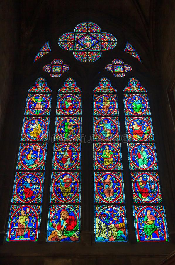 Closeup of a stained glass window in the Notre Dame de Paris Cathedral in Paris France. Paris, France - October 25, 2013: Closeup of a tall stained glass window stock image