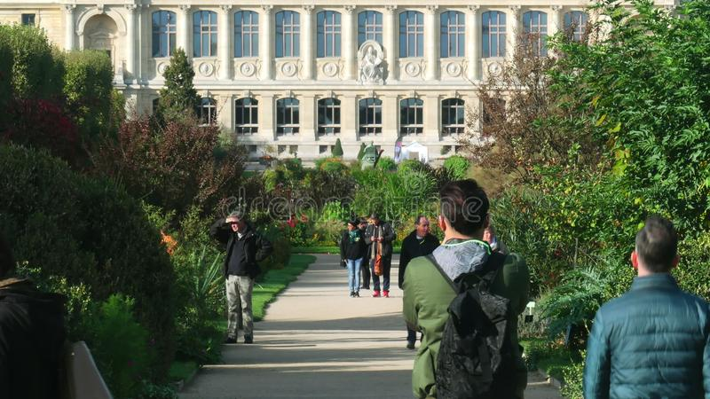 PARIS, FRANCE - OCTOBER 8, 2017. Crowded Jardin des plantes alley, the main botanical garden and facade of the grande royalty free stock images