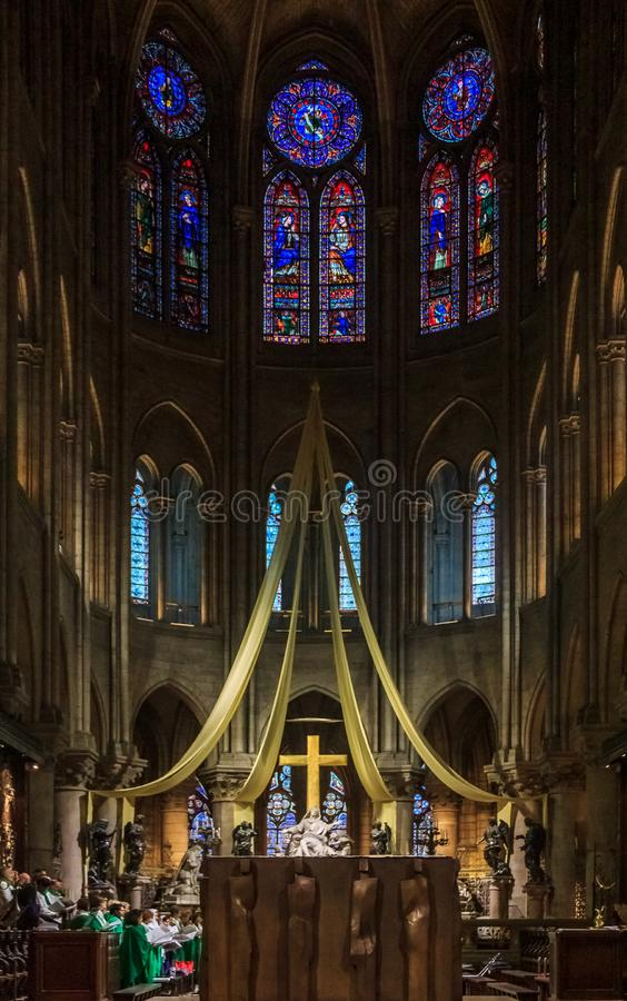 The altar and the cross of the Notre Dame de Paris Cathedral with the stained glass windows along the back wall in Paris France. Paris, France - October 25, 2013 stock photography