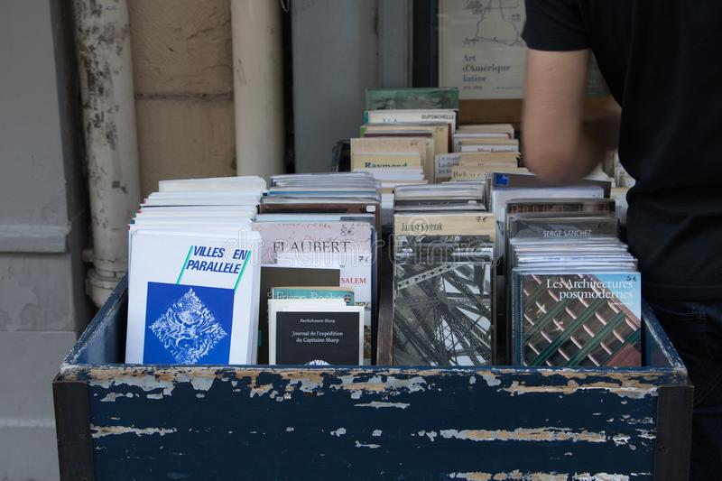 Used French books for stale at an outdoor bookstore on Rue de l`ecole in central Paris stock photos