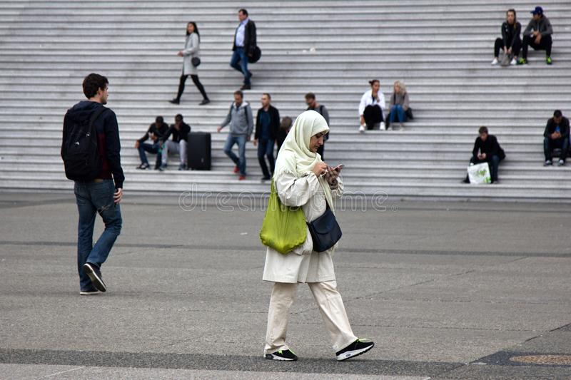 young Muslim woman in a headscarf in the city square stock images