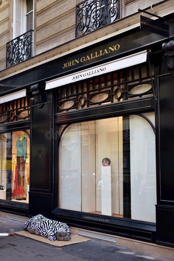Paris, France Un sans-abri dort sur des cartons devant une boutique luxueuse au quart de Marais images stock