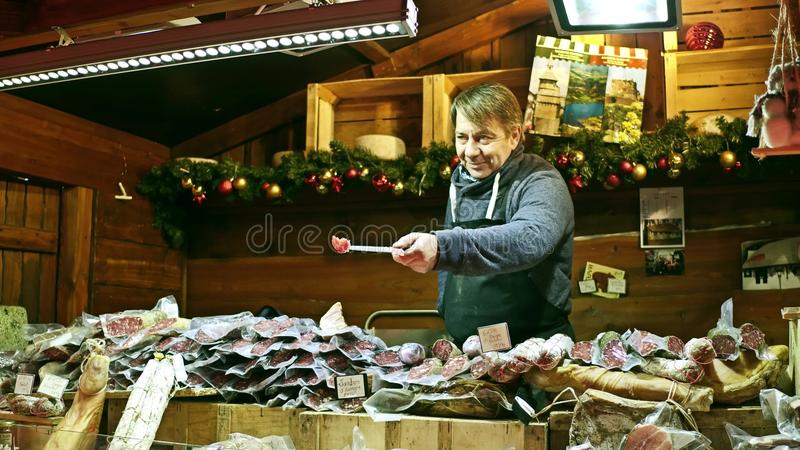 PARIS, FRANKREICH - DEZEMBER, 31 Weihnachts- und des neuen Jahresmarktlebensmittel klemmen Verkäufer fest Traditionelle Würste, F stockfotografie
