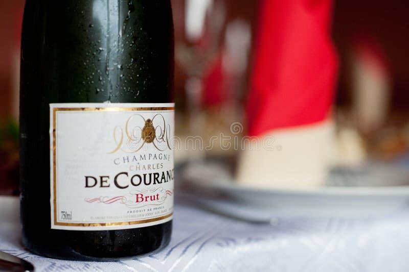 PARIS FRANKRIKE - APRIL 13, 2012: Förkylning och blöter flaskan av Charles de Courance Brut Champagne From Frankrike på tabellen royaltyfria bilder