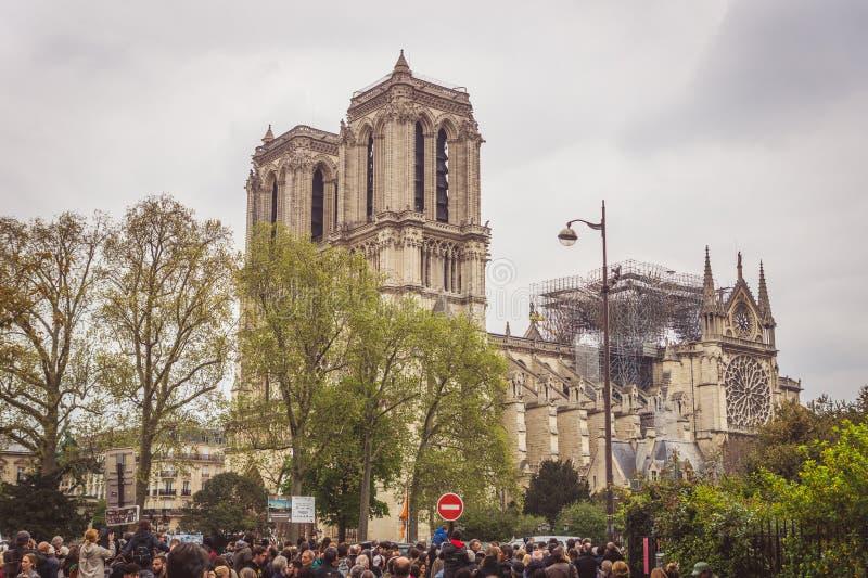 Paris Frankrike - April 16th, 2019: Folkmassa som framme står av domkyrkan Notre Dame de Paris efter den tragiska branden royaltyfria bilder