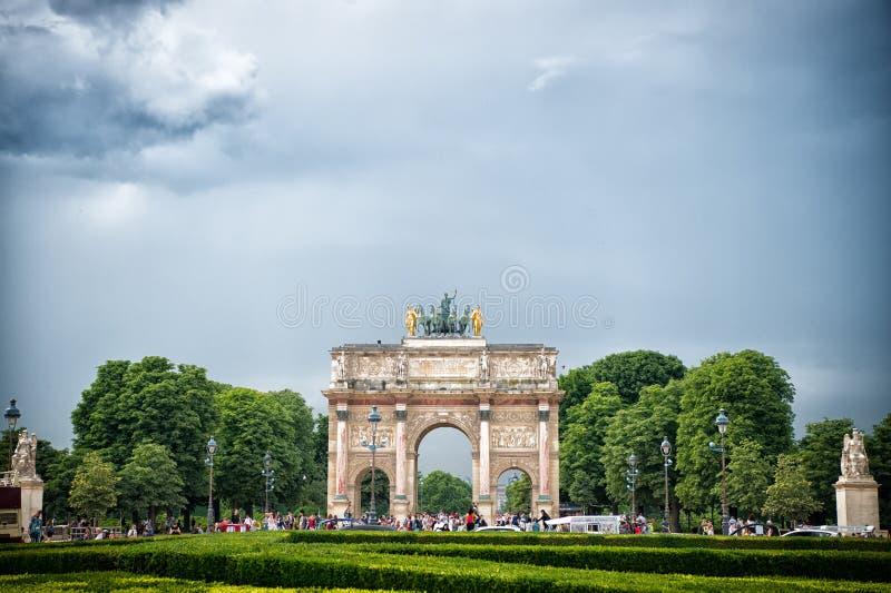 Paris Frankrike - Juni 02, 2017: Arc de Triomphe du Karusell i Louvreslott Ärke- monument och gröna träd på blå himmel _ royaltyfria bilder
