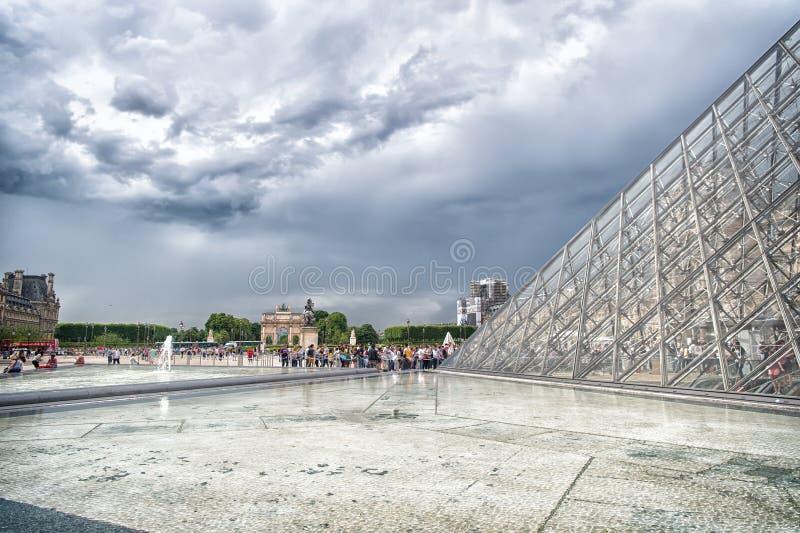 Paris Frankrike - Juni 02, 2017: borggården av Louvremuseet med den glass pyramiden och folket köar på molnig himmel Gränsmärke a royaltyfria foton
