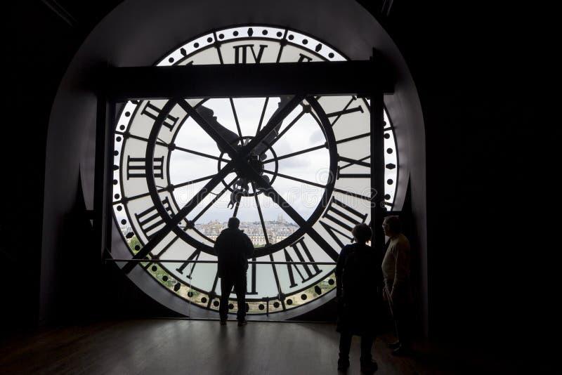 PARIS FRANKRIKE - MAJ 9, 2019: Berömd klocka med roman tal och konturn av mannen som ser in i runt fönster i det Orsay museet, arkivfoto