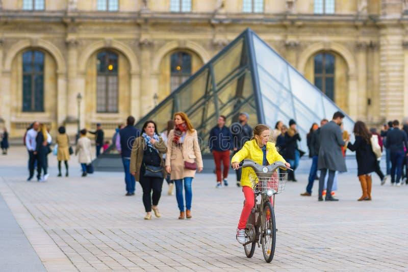 Paris Frankrike - Maj 1, 2017: Flicka som cyklar på Louvremuseet royaltyfri foto