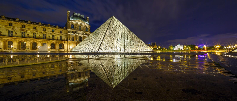 PARIS FRANKRIKE - MAJ 18, 2016: Louvremuseum och pyramiden i skymning royaltyfri foto