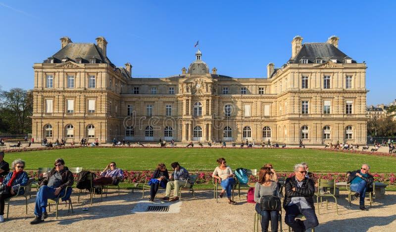 Paris Frankrike, mars 27 2017: Folket tycker om solig dag i den Luxembourg trädgården i Paris Den Luxembourg slotten är royaltyfri bild