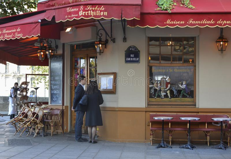 PARIS FRANKRIKE - OKTOBER 16, 2016: Ett par av män och kvinnor som studerar menyn i det berömda parisiska kafét Berthillon nära N royaltyfri fotografi