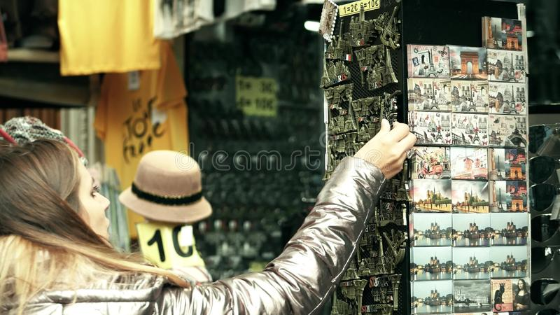 PARIS FRANKRIKE - OKTOBER 7, 2017 Ung kvinna som köper Eiffeltornsouvenirmagneten i ett turist- ställe arkivfoto
