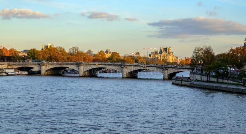 Paris im Herbst Die Sonne beleuchtet den Fluss die Seine, die gedrehten gelben Bäume an Land und die schönen Häuser, die ein Arch lizenzfreies stockbild