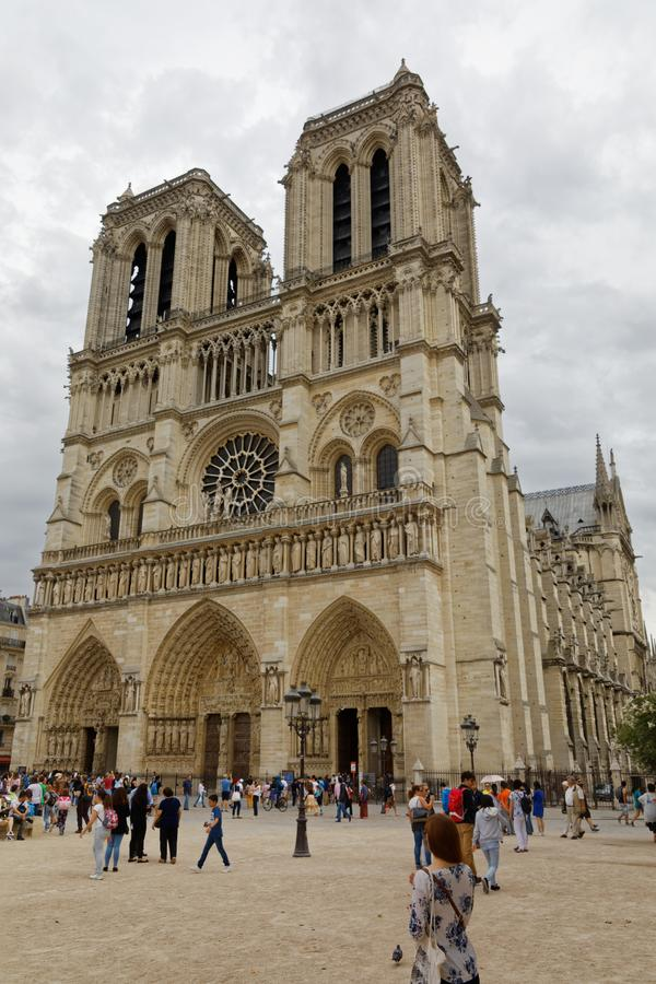 Notre Dame in Paris - angled view. Paris - July 31, 2017: Tourists admiring the exterior of Notre Dame on a cloudy day in Paris stock images