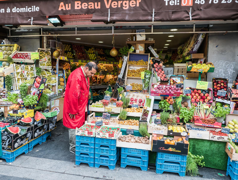 Paris-Ladenbesitzer überprüft sein Gemüse auf Fruchtstand lizenzfreies stockfoto