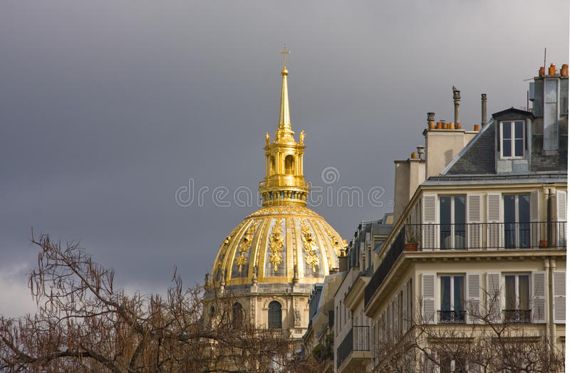 Paris Les Invalides apartment buildings. Dome and spire of Les Invalides behind and to side of apartment buildings in Paris. Dark, stormy sky sets off the gold royalty free stock images