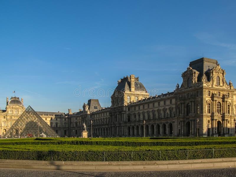 Paris - Louvremuseum och pyramid på solnedgången (färg) royaltyfri bild