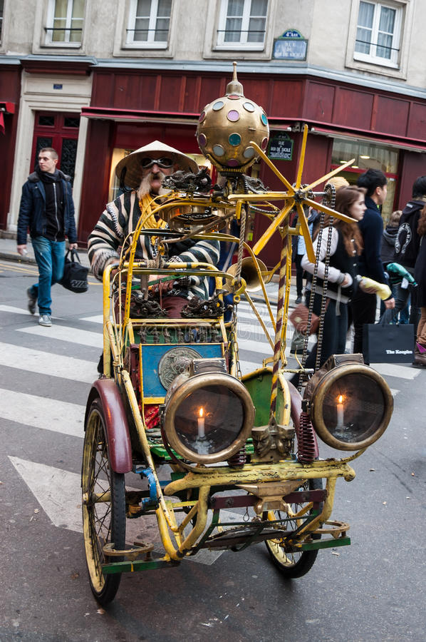 Extravagant senior rickshaw drives his unique antique vehicle in Paris. stock image