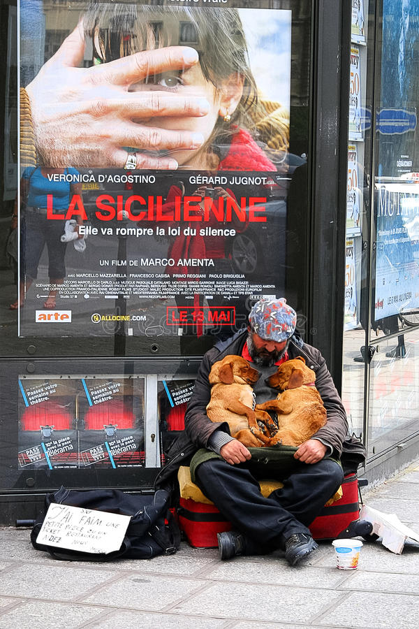 PARIS - May 7: A homeless man sitting on the street with a dog a stock photography