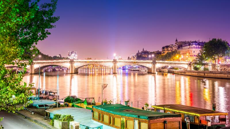 Paris at night. Seine in Paris at night with an old illuminated bridge royalty free stock image