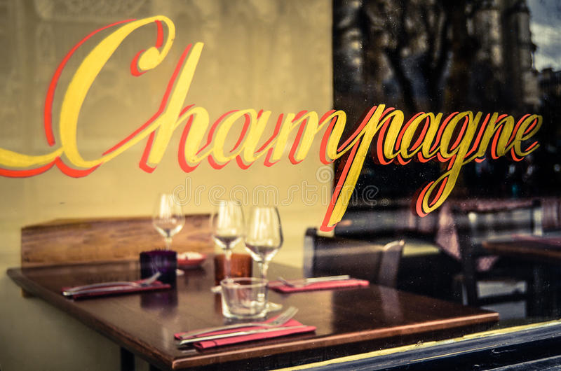 Paris Restaurant. With Champagne Sign In The Window With Place Settings And Wine Glasses stock photography
