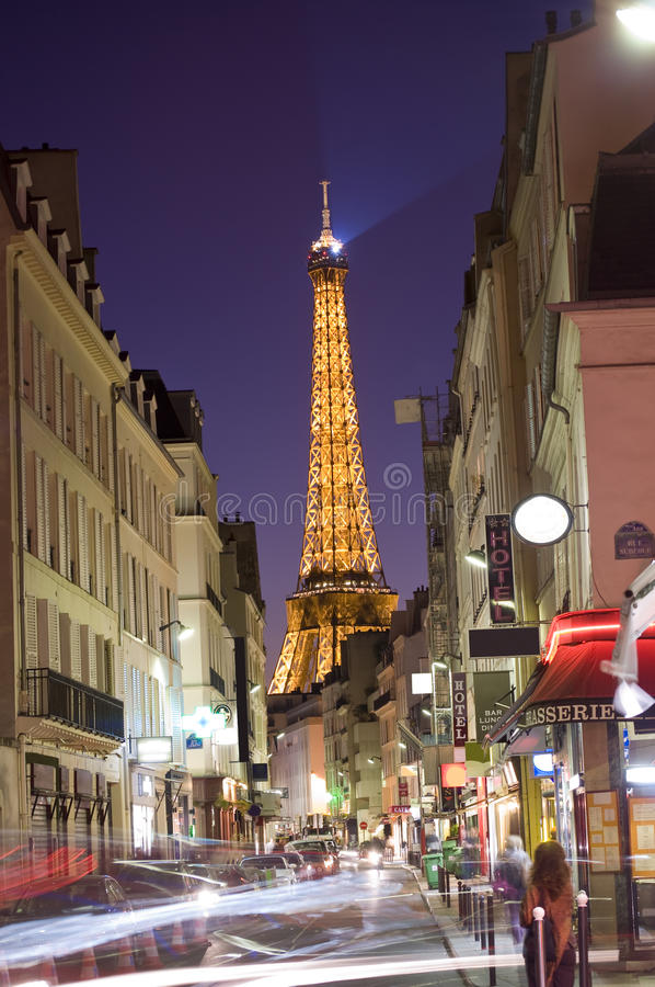 Paris rush hour. View looking down Rue St Dominique street in the 7th Arr. of Paris with the Eiffel Tower rising in the backround. Taken at dusk with long royalty free stock photos