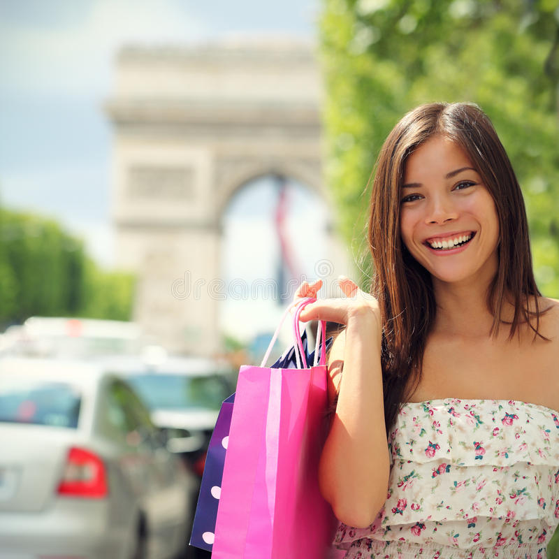 Paris Shopping Woman. Tourist on Champs-Élysées with Arc de Triomphe in the background carrying shopping bags outside in Paris. Pretty Asian Caucasian stock photography