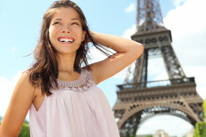 Paris travel woman tourist at Eiffel tower. Paris woman tourist at Eiffel Tower smiling happy. Beautiful Caucasian Asian girl enjoying her Paris travel royalty free stock images