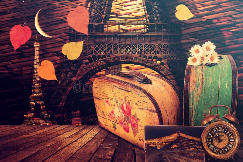 Paris voyage night dreams. Vintage suitcases, old clock, picture and flowers. Cobblestone pavement. Eiffel Tower lit by a bright moon. Parisian romantic love stock photo