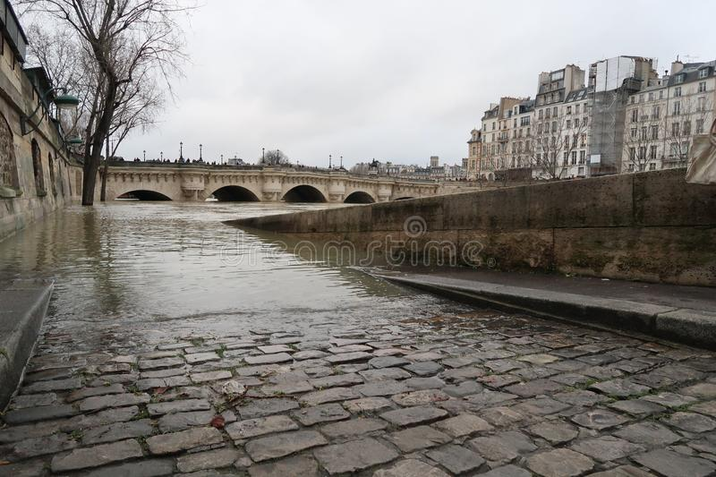 Paris, winter 2018, flood on the river Seine. Paris, winter 2018, flooding on the river Seine. Ramps under the water, pavement in the water, everything is gray stock photos
