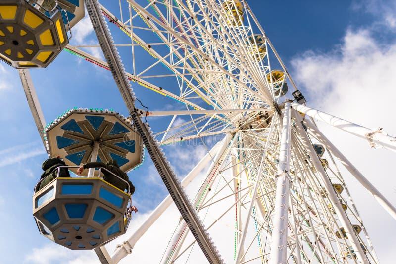 Pariserhjul med färgrika gondoler i en funfair, mot en härlig blå himmel med vita moln arkivfoto